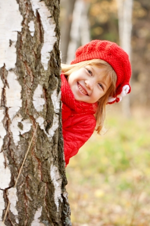 hide and seek: Cute happy little girl playing hide and seek outdoors