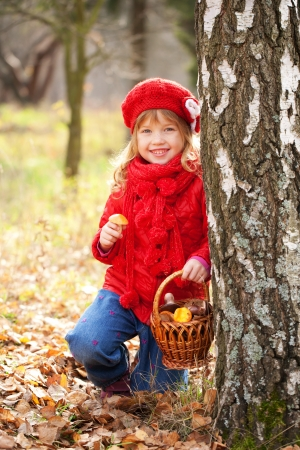 kids wear: Funny little girl with a basket filled with mushrooms in the autumn forest. Harvest concept.