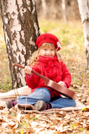 Funny little girl playing guitar in the forest Stock Photo - 23420734