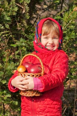 Divertida niña con una cesta llena de setas y manzanas en el bosque de otoño. Cosecha de concepto. Foto de archivo