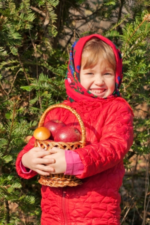 Funny little girl with a basket filled with mushrooms and apples in the autumn forest. Harvest concept. photo