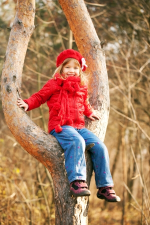 Funny little girl wearing a red sitting in a tree and smiling Stock Photo