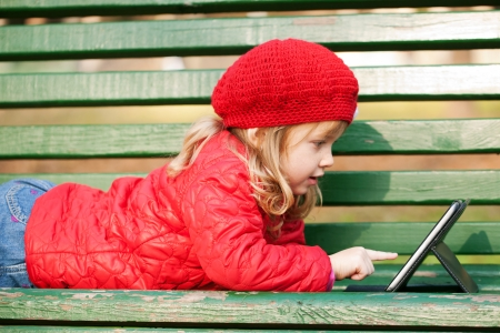 Happy little girl wearing red working with tablet pc and lying on bench in the park. photo
