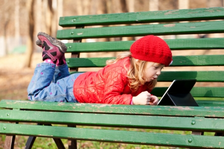 Happy little girl wearing a red working with tablet pc and lying on bench in the park. photo