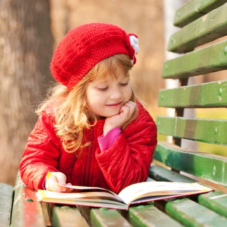 Little girl wearing a red reading a book on a bench in the park. photo