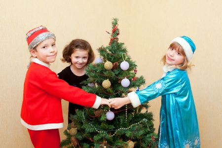 Children in carnival costumes dancing around the Christmas tree. Holiday concept. photo