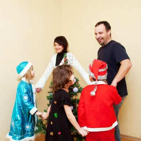 Family wearing in carnival costumes dancing around the Christmas tree. Holiday concept. photo