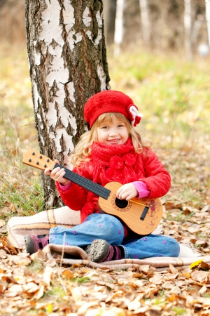 Lovely little girl playing guitar in the forest Stock Photo - 23480529