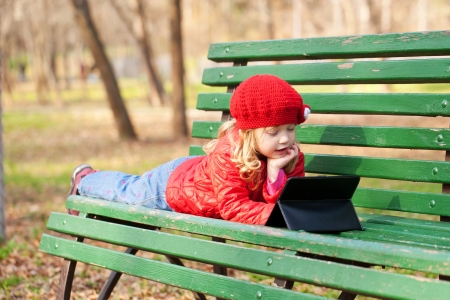 Funny little girl learning with tablet pc in the park. photo