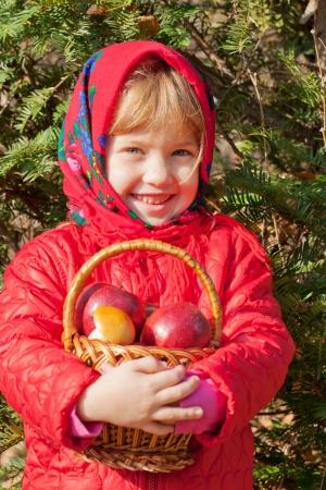 ni�o abrigado: Soleado d�a de oto�o. Sonrisa de la ni�a con las manzanas en una cesta