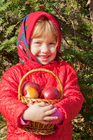 Sunny autumn day. Little smiling girl with apples in a basket photo