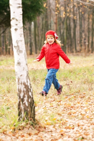 skip: Happy smiling little girl running in the birch forest Stock Photo