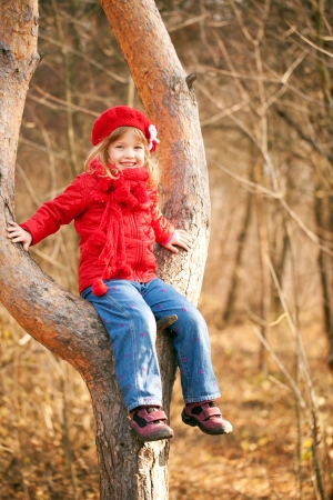 romp: Funny little girl wearing a red sitting in a tree and smiling Stock Photo