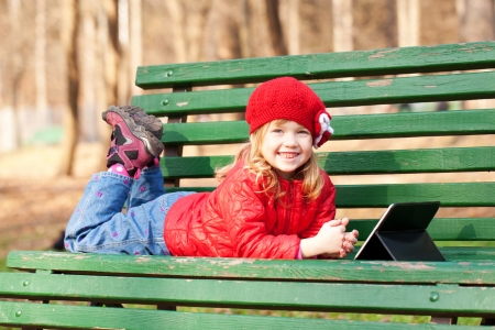 Portrait of a smiling happy little girl using tablet outdoors. photo