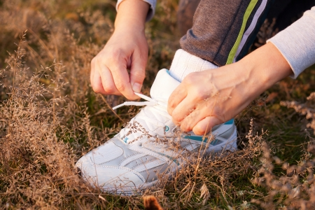 Womens hands tying the laces on sports shoes close up. Healthy lifestyle concept. Stock Photo