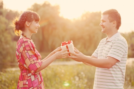 gift giving: Man giving to his woman a gift box. Happy middle-aged couple in love outdoors in the sunlight at sunset. Happy family concept. Retro style.