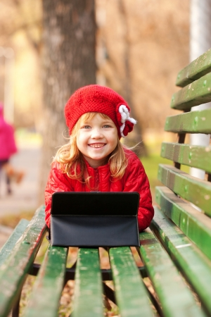 google play: Happy smiling little girl working with tablet pc and lying on bench in the park.