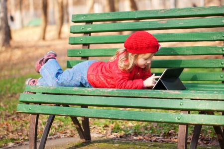 Happy smiling little girl working with tablet pc and lying on bench in the park. photo