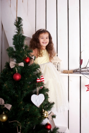 Happy elegant little girl  smiling and decorating the Christmas tree, enjoying the holidays. Christmas and New Year concept photo