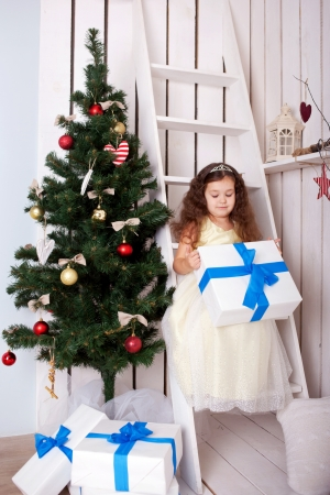 Happy elegant little girl holding gifts near the Christmas tree. Christmas, New Year, holiday concept photo