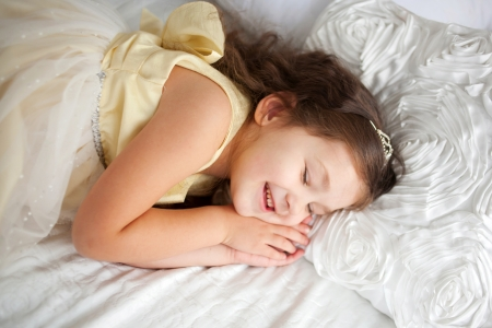 Pretty little girl sleeping and smiling in her sleep. Dream the little princess on a white bed close-up. photo