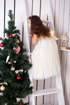 Happy elegant little girl climbing on ladder to decorate the Christmas tree. Christmas and New Year concept photo