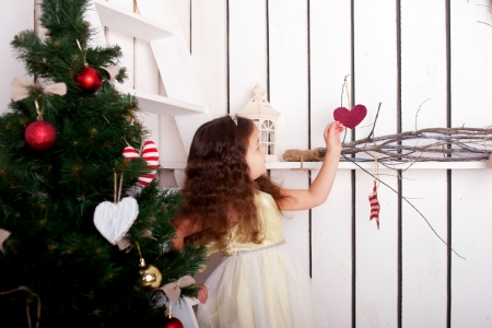 Happy elegant little girl climbing on ladder to decorate the Christmas tree and home  Christmas and New Year concept photo