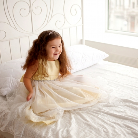 Pretty little girl waking up in the morning  Dream the little princess on a white bed  photo