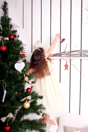 Happy little kid decorate the Christmas tree and home. Christmas and New Year concept photo