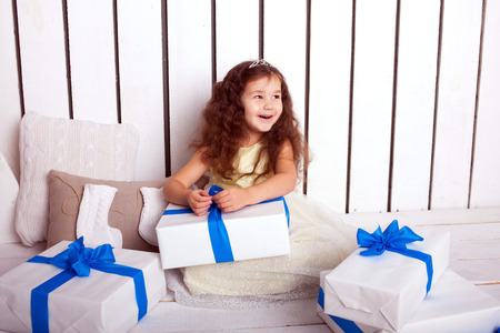 Happy smiling kid holding gifts. Christmas, New Year, holiday concept, ready for your text, letters or symbols. photo