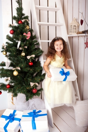 Happy smiling kid holding gifts near the Christmas tree. Christmas, New Year, holiday concept, ready for your text, letters or symbols. photo