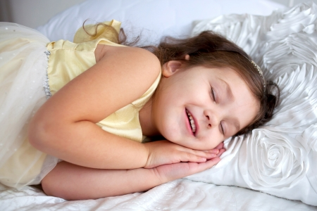 Happy smiling kid sleeping and smiling in her sleep. Dream the little princess on a white bed close-up. photo
