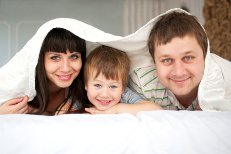 Happy family lying in bed and laughing early morning. Funny father, mother and child. Happy family concept. photo