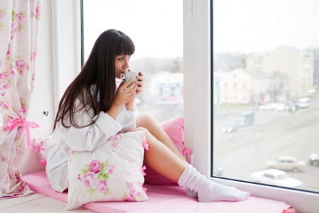 Pretty young woman drinking her morning coffee, sitting on the window sill and looking out the window.