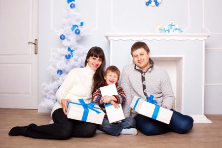 christmas morning: Funny family holding gifts near the fireplace and Christmas tree. Christmas, New Year, holiday concept.  Stock Photo