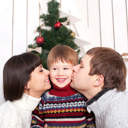 happy family concept: Mother and father kissing their kid in the morning Christmas Eve. Homemade Christmas and happy family concept Stock Photo