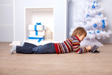 Happy child using a tablet PC near the Christmas tree and fireplace. Computer Generation concept. photo