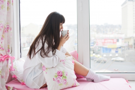 sill: Lovely young woman drinking her morning coffee, sitting on the window sill and looking out the window.