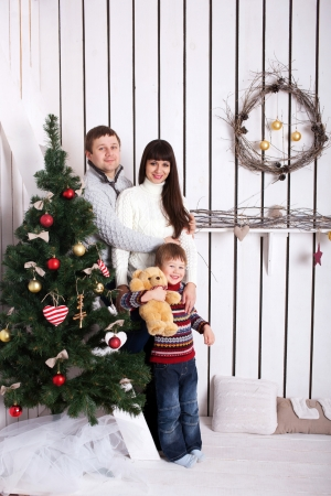Happy family near the Christmas tree. Christmas, New Year, holiday concept. photo