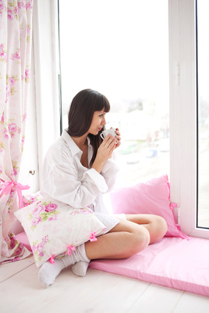 Pretty young woman drinking her morning coffee, sitting on the window sill and looking out the window. Morning and waking concept. photo