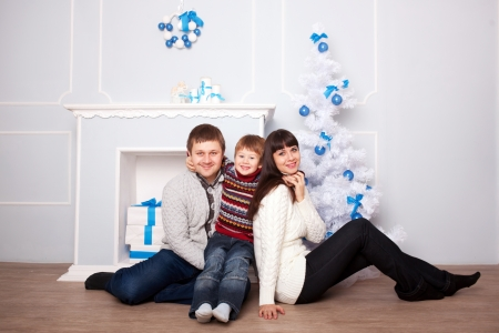 christmas morning: Funny family hugging near the fireplace and Christmas tree. Christmas, New Year, holiday concept.