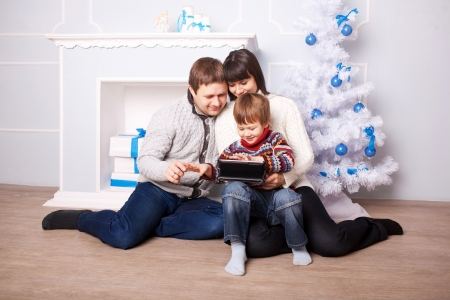 Funny family using the tablet near the fireplace and Christmas tree. Father, mother and child, smiling family with tablet pc looking at something and laughing. photo