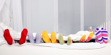 Happy family concept. Feet of father, mother and four children in colorful knitted socks on white bed. Family sleeping together. photo