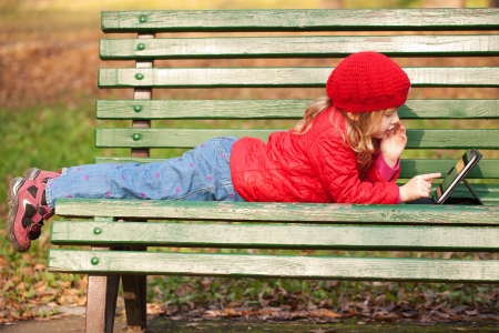 Happy little kid working with tablet pc and lying on bench in the park.
