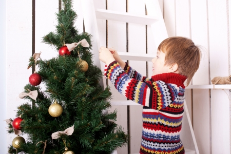 child ball: Happy child decorating the Christmas tree with balls. Christmas Eve concept. Stock Photo