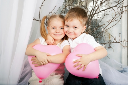 Little boy and girl romantic couple in love. Little kids hugging and holding heart balloons. Valentines Day and love concept photo