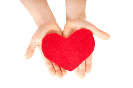 Children hands giving red heart made from felt. Love and care concept. photo