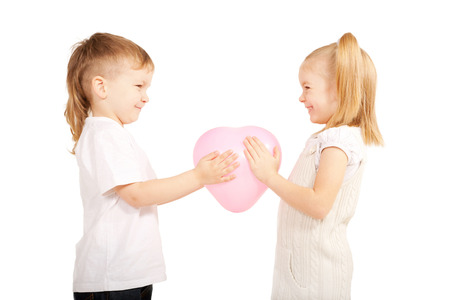 Little children, a boy and girl holding pink heart and looking at each other eye to eye. Love and valentines day concept. Isolated on white  Stock Photo