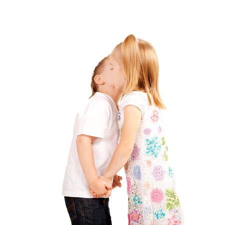 Couple of kids, boy and girl holding hands and kissing. Love and valentines day concept. Isolated on white  photo