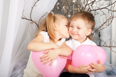 Little couple of kids hugging, kissing and holding heart balloons. Valentine's Day and love concept.  photo